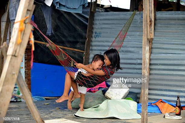 STORY 'PhilippinesFloodPoverty' by Cecile Morella on this photo taken on June 11 a girl comforts her baby brother on their shanty house made of...