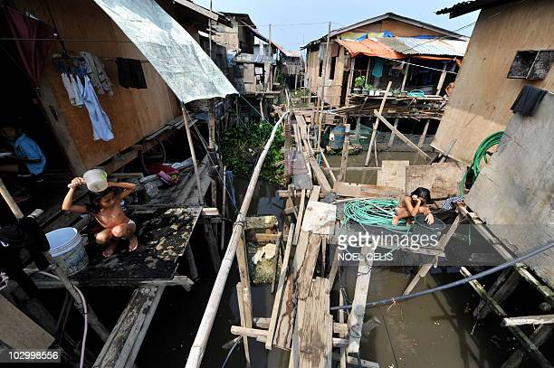 STORY 'PhilippinesFloodPoverty' by Cecile Morella on this photo taken on June 11 children have a bath outside their shanty houses linked by flimsy...