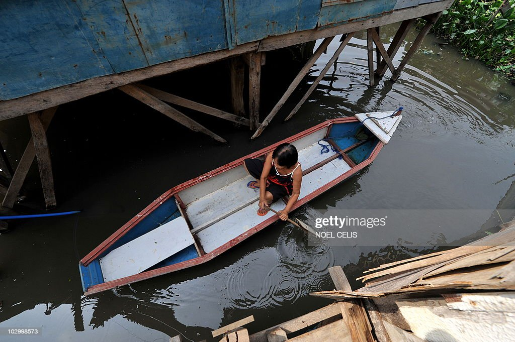 STORY 'Philippines-Flood-Poverty' by Cecile Morella (FILES) on this photo taken on June 11, 2010, a woman paddles on a wooden boat to her shanty house made of plywood and metal sheets sitting precariously on thin stilts above the garbage-flecked water hyacinth beds on the shore of Laguna Lake in Manila. Hundreds of thousands of slum dwellers persist in living in dangerous areas in the Philippine's capital despite deadly floods that claimed hundreds of lives last year. A month into the tropical nation's annual rainy season entire communities that were hit hard by the September 2009 disaster are vigorously resisting government efforts to move them to safer. AFP PHOTO / NOEL CELIS / FILES