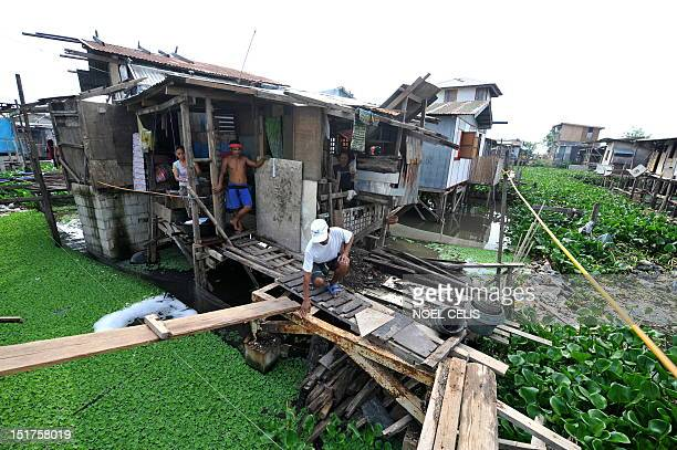 STORY 'PhilippinesFloodPoverty' by Cecile Morella on this photo taken on June 11 a man checks the flimsy wooden footbridges used to cross to his...