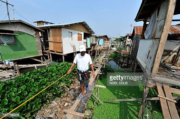 STORY 'PhilippinesFloodPoverty' by Cecile Morella on this photo taken on June 11 a man walks on a flimsy wooden footbridges to cross to his shanty...