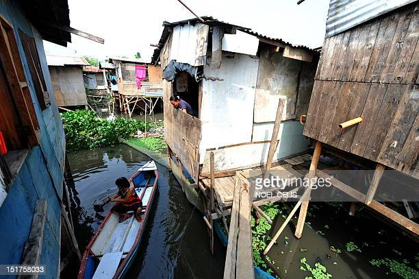 STORY 'PhilippinesFloodPoverty' by Cecile Morella on this photo taken on June 11 a woman paddles on a wooden boat to her shanty house made of plywood...