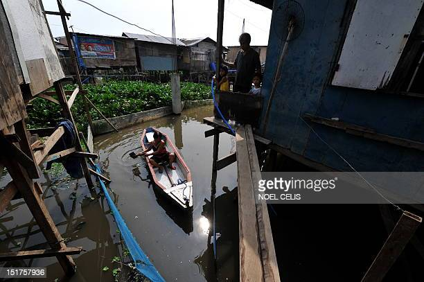 STORY 'PhilippinesFloodPoverty' by Cecile Morella This photo taken on June 11 shows a woman on a wooden boat paddling to her shanty house made of...