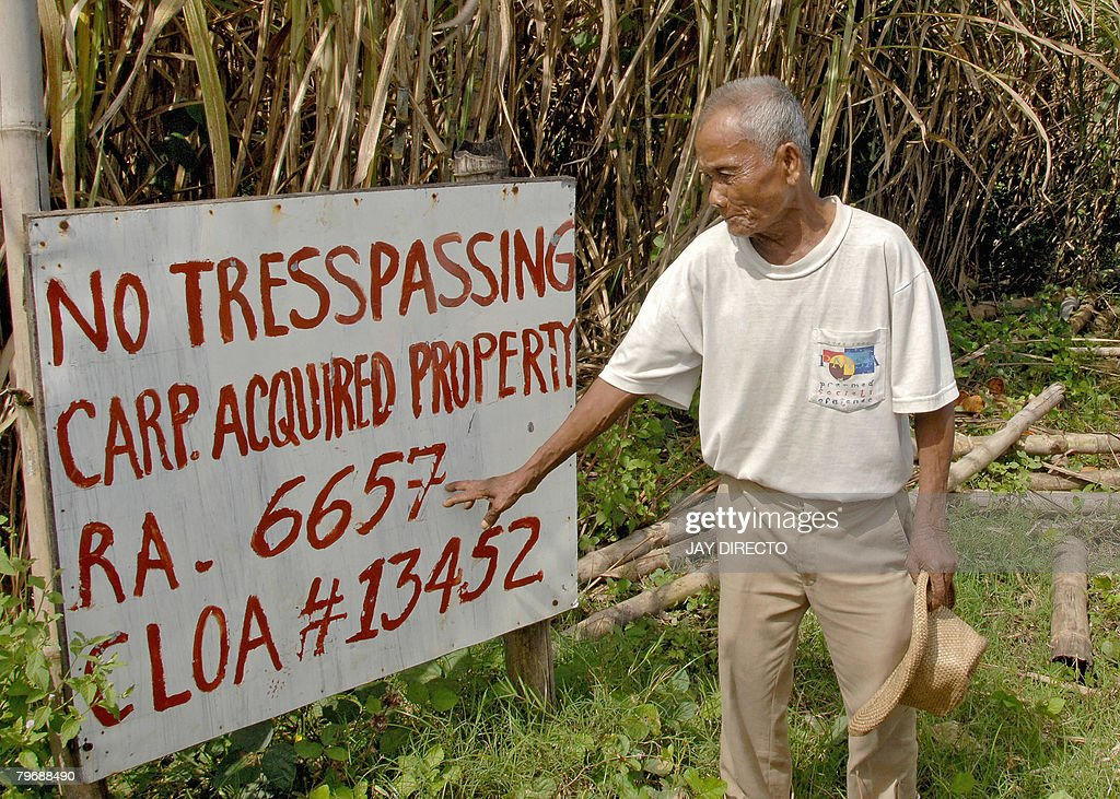 STORY 'Philippines-food-prices-inflation-farm-reform,FEATURE' by Cecil Morella Farmer Eugenio Alpar show a sign with the inscription 'No Trespassing CARP Acquired Property' on the land that he fought for 20 years to keep, in Escalante on the central Philippine island of Negros on February 1, 2008. For more than 20 years farmer Eugenio Alpar has been fighting for the right to own the land he tills on the central Philippine island of Negros. Now that his dream is in sight the 72-year-old activist for land reform says he may be too old to do anything with it. In 1988 the Philippine government introduced an agrarian land reform programme in which it promised to lift millions out of poverty and give farm workers the right to own land. AFP PHOTO/Jay DIRECTO