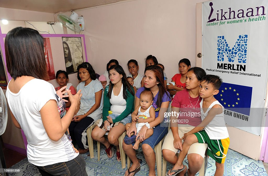 Philippines-politics-population-religion,FOCUS Philippines-politics-population-religion,FOCUS In this photo taken January 16, 2013, a health worker (L) at the Likhaan Center for Women's Health educates mothers about different kinds of birth control, a massive slum in Manila where more than 60,000 people compete for space. A historic birth control law that took effect in the Philippines on January 17 requires government health centres to hand out free condoms and birth control pills, benefiting tens of millions of the country's poor who would not otherwise be able to afford or have access to them. AFP PHOTO / Jay DIRECTO