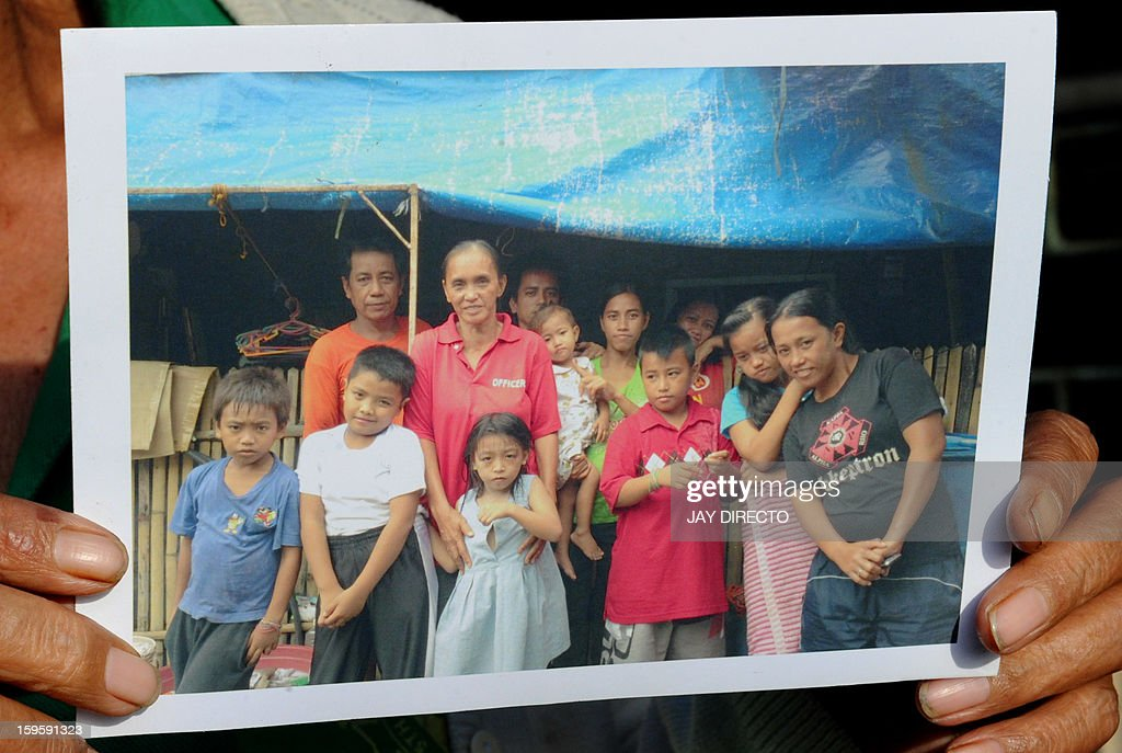 Philippines-politics-population-religion,FOCUS Philippines-politics-population-religion,FOCUS In this photo taken January 16, 2013, Rosalie Cabenan shows a photo of some of her 22 children at their home in Baseco, a massive slum in Manila where more than 60,000 people compete for space. A historic birth control law that took effect in the Philippines on January 17 after years of opposition from the Catholic Church came too late for Rosalie Cabenan, a housewife who has given birth 22 times. AFP PHOTO / Jay DIRECTO