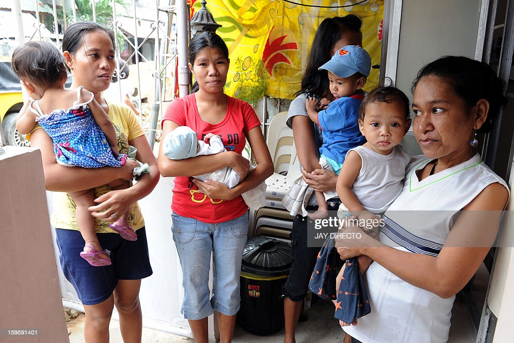 Philippines-politics-population-religion,FOCUS Philippines-politics-population-religion,FOCUS In this photo taken January 16, 2013, mothers with their children queue for family planning services at the Likhaan Center for Women's Health in Baseco, a massive slum in Manila where more than 60,000 people compete for space. A historic birth control law that took effect in the Philippines on January 17 requires government health centres to hand out free condoms and birth control pills, benefiting tens of millions of the country's poor who would not otherwise be able to afford or have access to them. AFP PHOTO / Jay DIRECTO