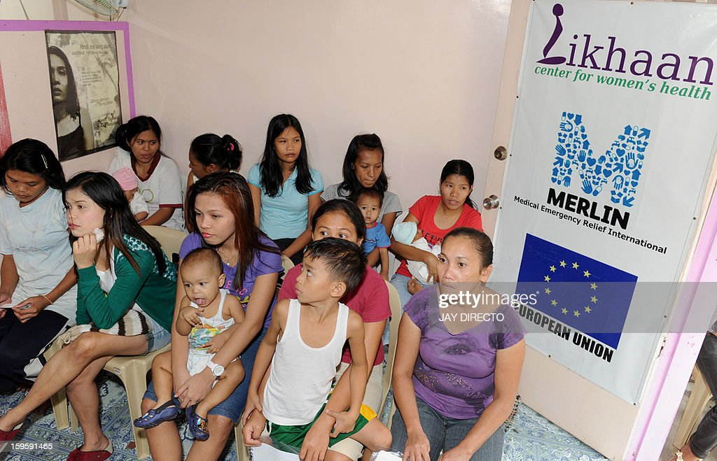 Philippines-politics-population-religion,FOCUS Philippines-politics-population-religion,FOCUS In this photo taken January 16, 2013, mothers with their children wait for family planning services at the Likhaan Center for Women's Health in Baseco, a massive slum in Manila where more than 60,000 people compete for space. A historic birth control law that took effect in the Philippines on January 17 requires government health centres to hand out free condoms and birth control pills, benefiting tens of millions of the country's poor who would not otherwise be able to afford or have access to them. AFP PHOTO / Jay DIRECTO