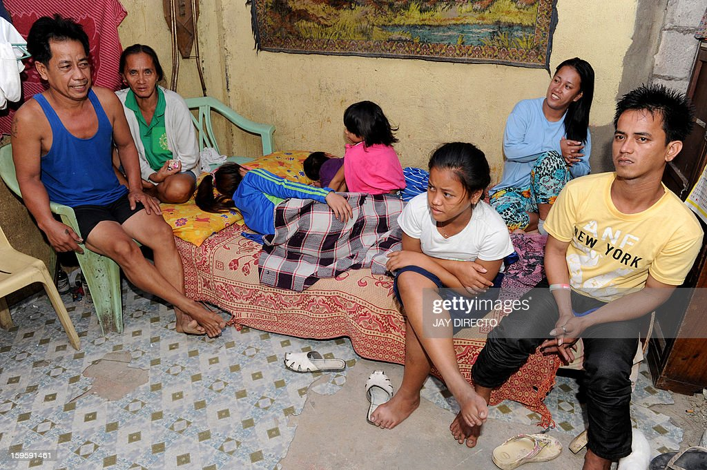 Philippines-politics-population-religion,FOCUS Philippines-politics-population-religion,FOCUS Rosalie Cabenan (2nd L) with her husband Danilo (L) pose with some of their children at their home in Baseco, a massive slum in Manila where more than 60,000 people compete for space, on January 17, 2013. A historic birth control law that took effect in the Philippines on January 17 after years of opposition from the Catholic Church came too late for Rosalie Cabenan, a housewife who has given birth 22 times. AFP PHOTO / Jay DIRECTO
