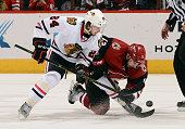 Phillip Danault of the Chicago Blackhawks and Brad Richardson of the Arizona Coyotes battle for a faceoff during the third period at Gila River Arena...