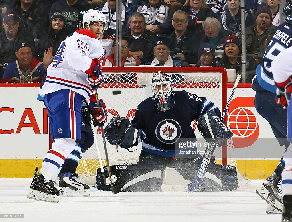 Phillip Danault #24 of the Montreal Canadiens and goaltender Michael Hutchinson #34 of the Winnipeg Jets keep an eye on the flying puck during second period action at the MTS Centre on January 11, 2017 in Winnipeg, Manitoba, Canada.