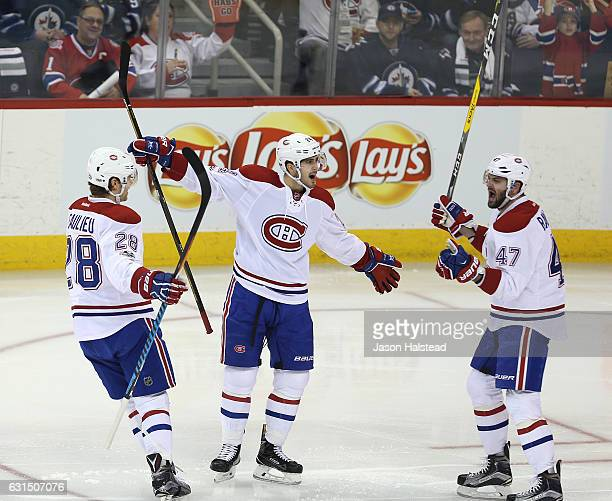 Phillip Danault of the Montreal Canadiens celebrates his goal against the Winnipeg Jets with Nathan Beaulieu and Alexander Radulov during NHL action...