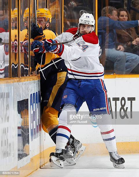 Phillip Danault of the Montreal Canadiens checks Mattias Ekholm of the Nashville Predators into the boards during an NHL game at Bridgestone Arena on...