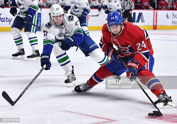 Phillip Danault of the Montreal Canadiens controls the puck against Ben Hutton of the Vancouver Canucks in the NHL game at the Bell Centre on...
