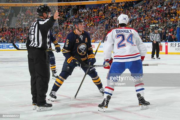 Phillip Danault of the Montreal Canadiens is removed from a faceoff against Jack Eichel of the Buffalo Sabres by linesman Mark Shewchyk during an NHL...