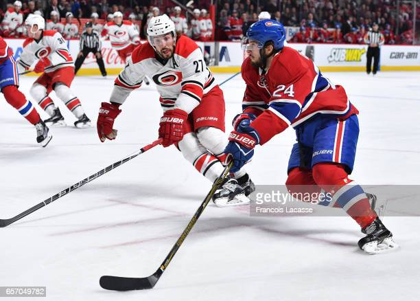 Phillip Danault of the Montreal Canadiens skates with the puck against Justin Faulk of the Carolina Hurricanes in the NHL game at the Bell Centre on...