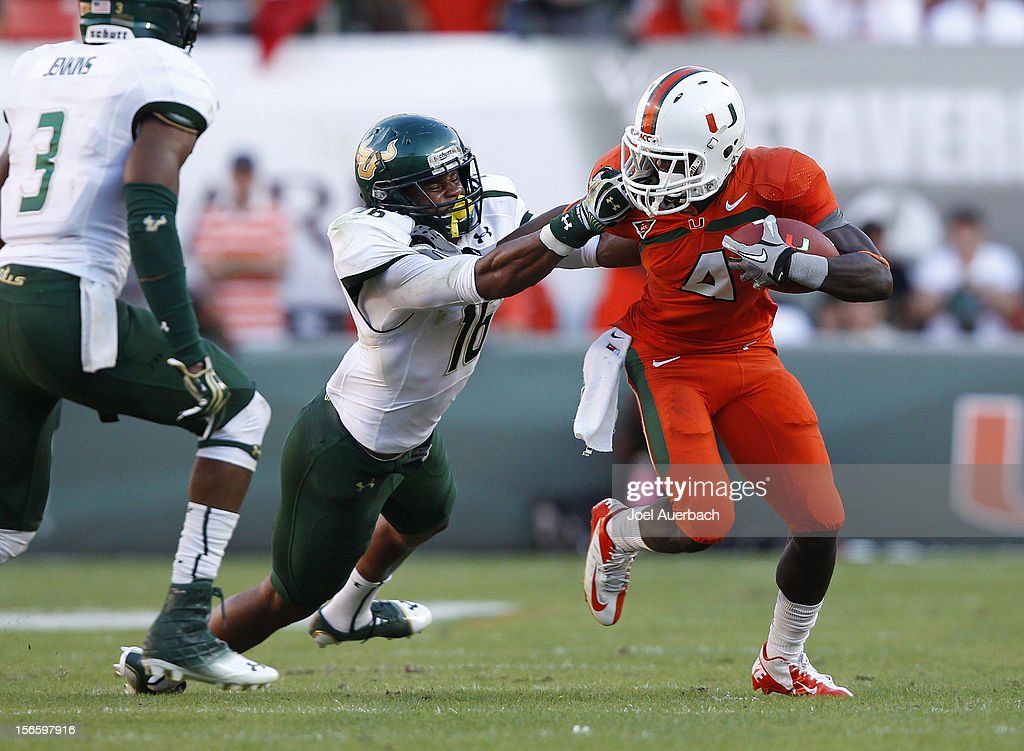 Phillip Dorsett #4 of the Miami Hurricanes runs with the ball and is tackled by Reshard Cliett #16 of the South Florida Bulls who received a face mask penalty on the play on November 17, 2012 at Sun Life Stadium in Miami Gardens, Florida.