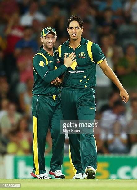 Phillip Hughes and Mitchell Johnson celebrate the run out of Kieron Pollard of the West Indies during the Commonwealth Bank One Day International...