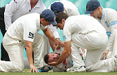 Phillip Hughes of South Australia is helped by New South Wales players after falling to the ground after being struck in the head by a delivery...