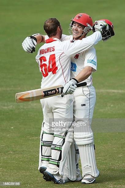Phillip Hughes of the Redbacks is congratulated by teammate Travis Head after reaching 200 runs during day three of the Sheffield Shield match...