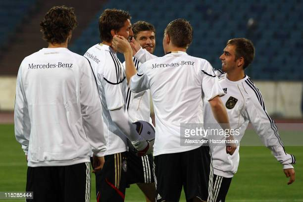 Phillip Lahm of Germany jokes with his team mates Toni Kroos Thomas Mueller Rene Adler and Mats Hummels during a training session ahead of their UEFA...