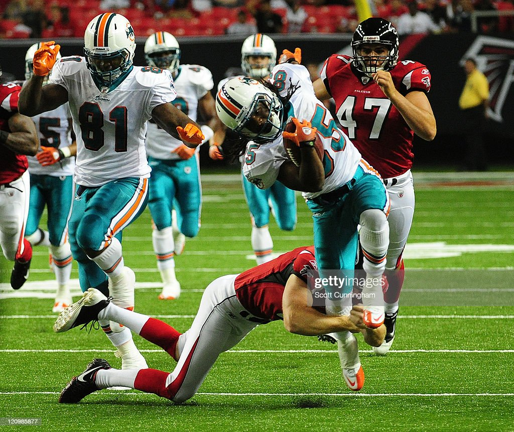 Phillip Livas #85 of the Miami Dolphins breaks a tackle against Ken Parrish #6 of the Atlanta Flacons to score a touchdown on a punt return during a preseason game at the Georgia Dome on August 12, 2011 in Atlanta, Georgia.