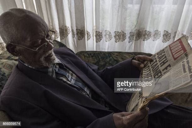 Phillip Mabelane reads a copy of a 1977 newspaper at his son Lasch Mabelane's home in Diepkloof South Africa on September 29 2017 For 40 years he has...