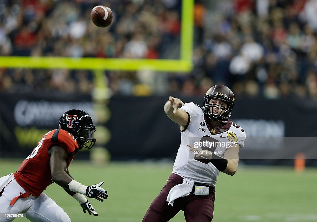 Phillip Nelson #9 of Minnesota looks to pass as he is pressured by Micah Awe #18 of Texas Tech during the Meineke Car Care of Texas Bowl at Reliant Stadium on December 28, 2012 in Houston, Texas.