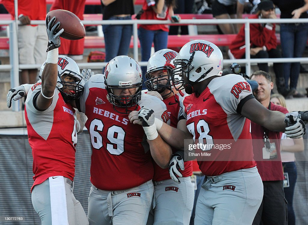 Phillip Payne #4 of the UNLV Rebels celebrates with teammates after scoring a 31-yard touchdown against the Colorado State Rams during their game at Sam Boyd Stadium October 29, 2011 in Las Vegas, Nevada. The score was Payne's 25th touchdown reception, breaking the all-time record for UNLV football players. UNLV won the game 38-35.