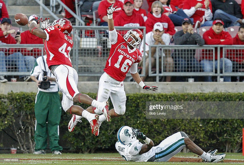 Phillip Steward #42 and Adrian McDonald #16 of the Houston Cougars attempt to intercept a pass as Ryan Grant #3 of the Tulane Green Wave falls down at Robertson Stadium on November 24, 2012 in Houston, Texas. Houston defeats Tulane 40-17.