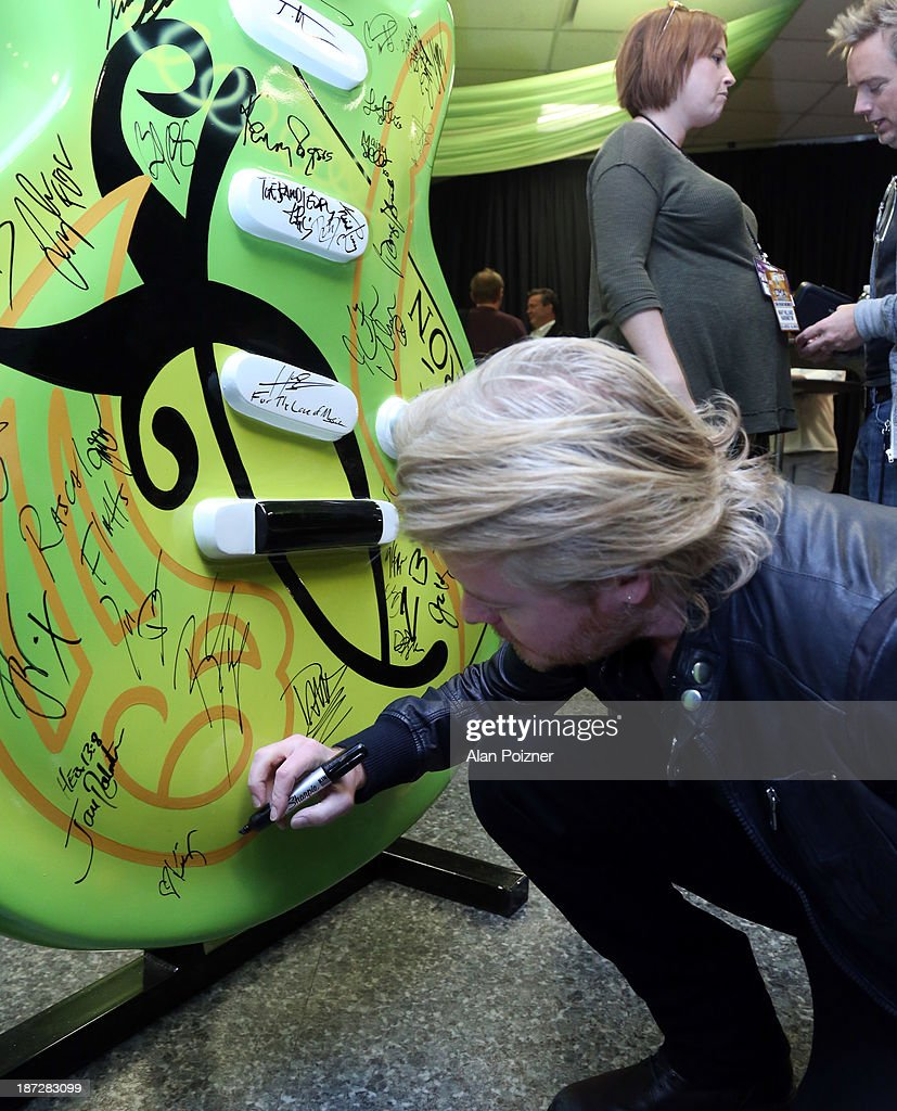Phillip Sweet of Little Big Town signs a giant Patron tequila guitar backstage at the CMA Awards to benefit the 'Keep the Music Playing' music education on November 3, 2013 in Nashville, Tennessee.