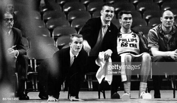 Phillips 66 assistant coach Bobby Plump drops to all fours to get a better look at proceedings during Phillips close call against Dayton Ohio in...