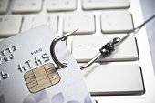 phishing - fish hook with a credit card on white computer keyboard