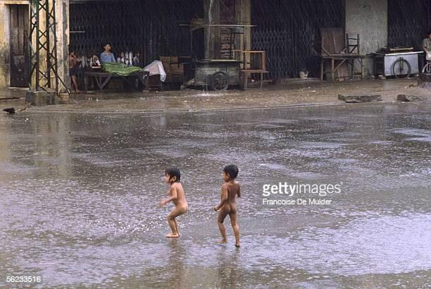Phnom Penh Nude children under the rain during the monsoon June 1989