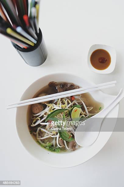 Pho in a white bowl on a white table