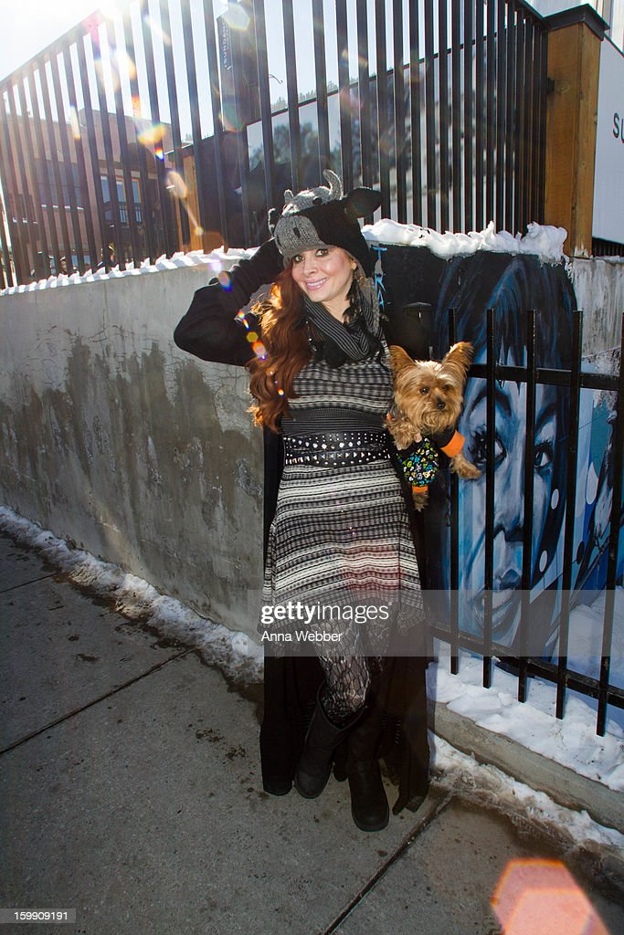 Phoebe Price, actress from Los Angeles, wearing Phoebe Price Designs hat, Diane Von Furstenberg dress, Phoebe Price Designs feather earrings, Georgio Armani sweater, and Bearpaw boots on January 22, 2013 in Park City, Utah.