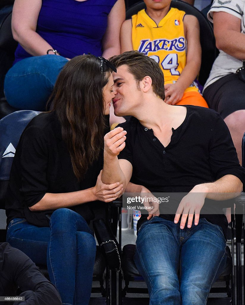 Phoebe Tonkin and Paul Wesley kiss at a basketball game between the Atlanta Hawks and the Los Angeles Lakers at Staples Center on March 15 2015 in...