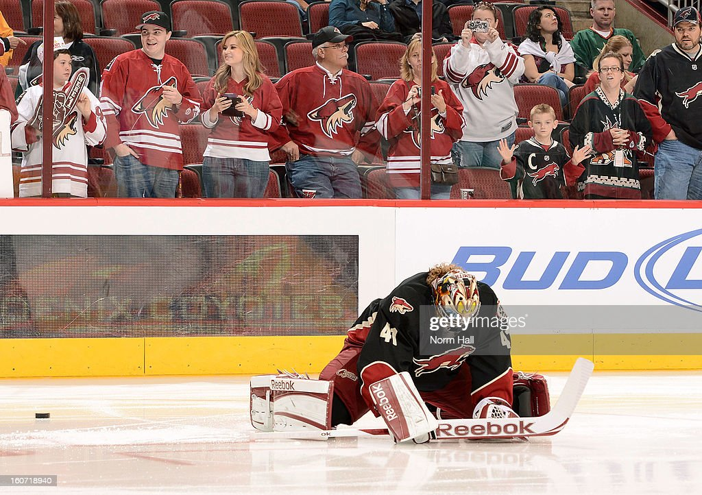 Phoenix Coyotes fans watch as Coyotes Goaltender Mike Smith #41 warms up during pregame against the Minnesota Wild at Jobing.com Arena on February 4, 2013 in Glendale, Arizona.