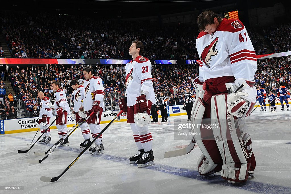 Phoenix Coyotes players line up for the singing of the national anthem prior to a game against the Edmonton Oilers on February 23, 2013 at Rexall Place in Edmonton, Alberta, Canada.