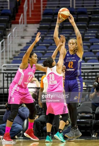Phoenix Mercury center Brittney Griner holds the ball high above Washington Mystics guard Kristi Toliver and center Krystal Thomas during a WNBA game...
