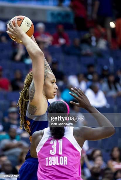 Phoenix Mercury center Brittney Griner holds the ball high over Washington Mystics forward Asia Taylor during a WNBA game on August 18 between the...