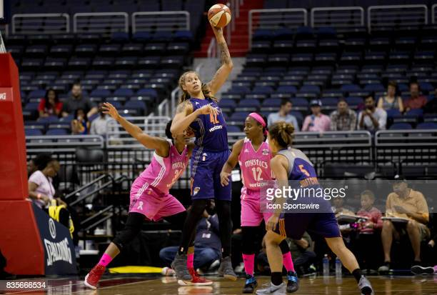 Phoenix Mercury center Brittney Griner holds the ball high over Washington Mystics guard Ivory Latta during a WNBA game on August 18 between the...