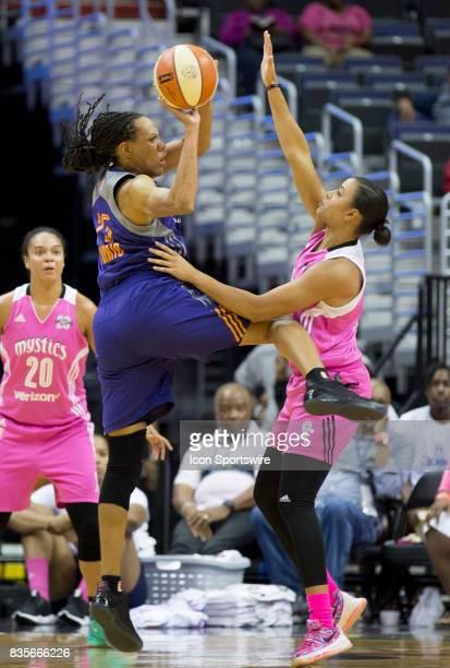 Phoenix Mercury forward Monique Currie passes over Washington Mystics guard Natasha Cloud during a WNBA game on August 18 between the Washington...