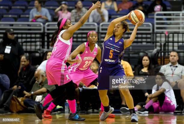 Phoenix Mercury guard Leilani Mitchell holds the ball away from Washington Mystics guard Ivory Latta during a WNBA game on August 18 between the...