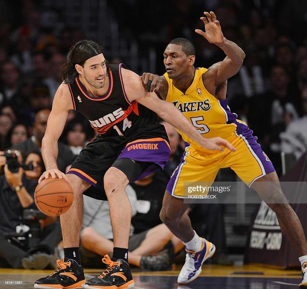Phoenix Suns Argentinian player Luis Scola (L) is defended by the Los Angeles Lakers Metta World Peace during their NBA basketball match at Staples Center in Los Angeles, California, February 12, 2013. The Lakers defeated the Suns, 91-85. AFP PHOTO Robyn BECK