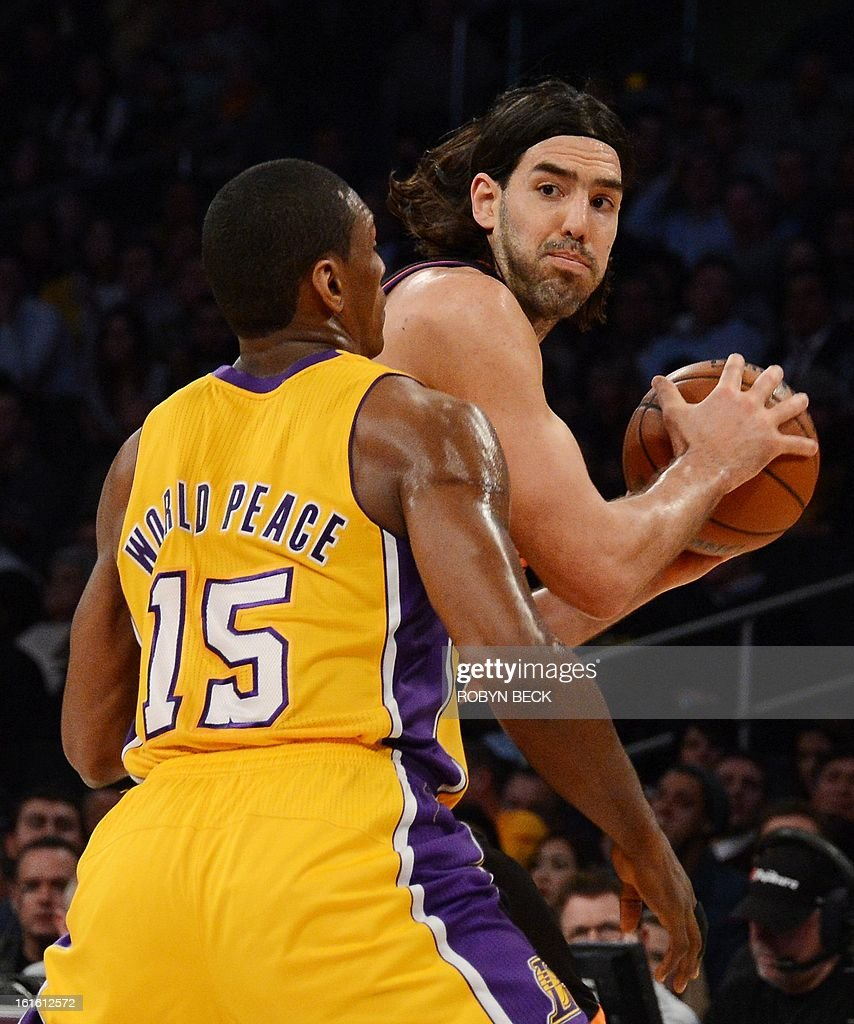 Phoenix Suns Argentinian player Luis Scola (R) looks to pass against the Los Angeles Lakers Metta World Peace during their NBA basketball match at Staples Center in Los Angeles, California, February 12, 2013. The Lakers defeated the Suns, 91-85. AFP PHOTO Robyn BECK