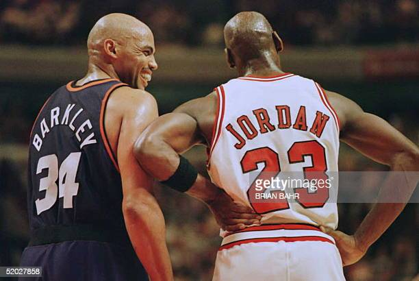 Phoenix Suns forward Charles Barkley laughs at a foul call with Chicago Bulls guard Michael Jordan in the first half 28 January 1996 at the United...