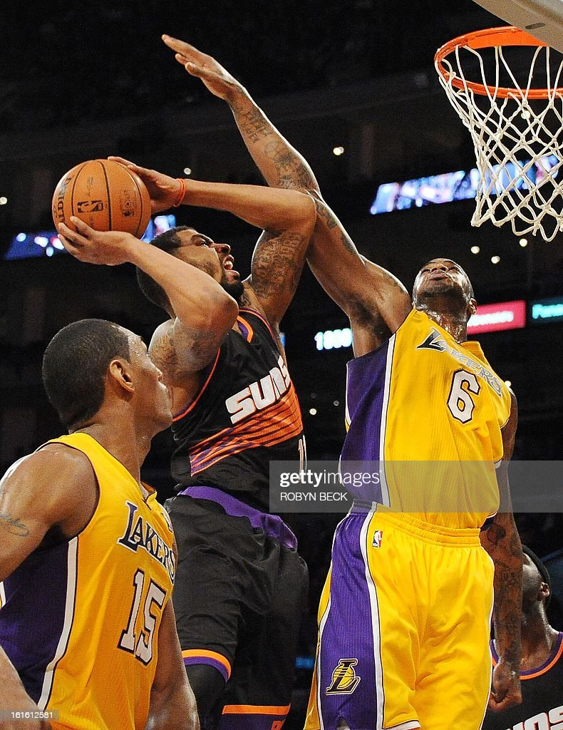 Phoenix Suns Markieff Morris (C) is blocked by Los Angeles Lakers Earl Clark (R) during their NBA match at Staples Center in Los Angeles, California, February 12, 2013. The Lakers defeated the Suns, 91-85. AFP PHOTO Robyn BECK