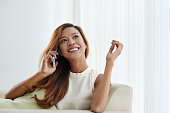 Portrait of pretty Asian woman talking on the phone