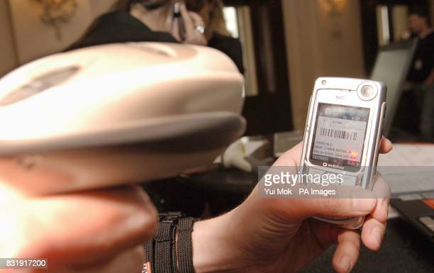 A phone displaying a barcode and text message ticket getting scanned for entrance into Snow Patrol's exclusive one off gig at The Royal Opera House...
